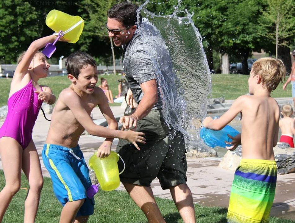 kids throwing water on adult